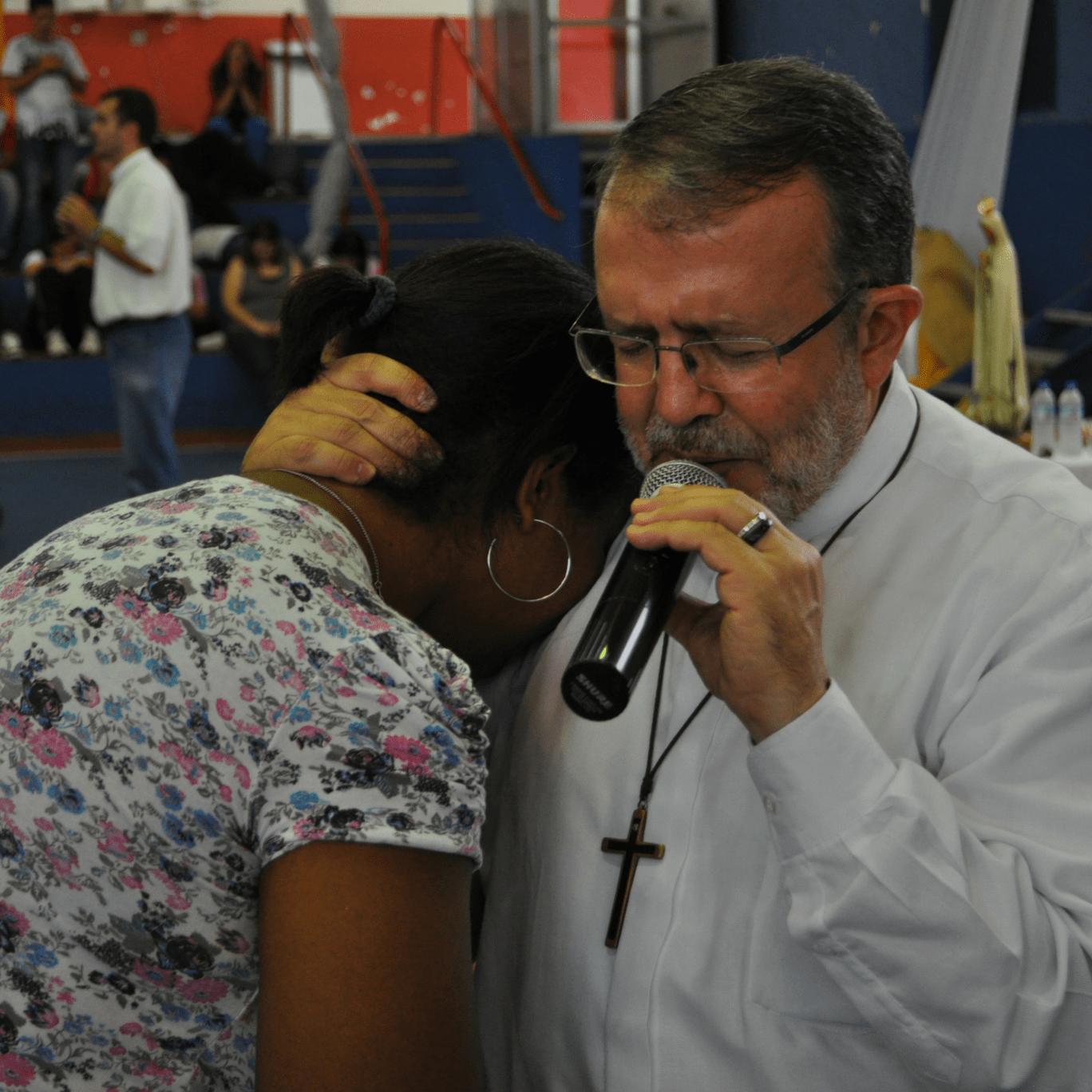 Padre Henrique abraça um mulher que chora