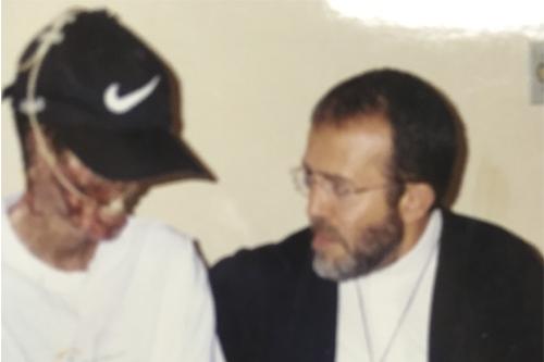 Paulo Roberto com os rosto desfigurado ao lado de Padre João Henrique