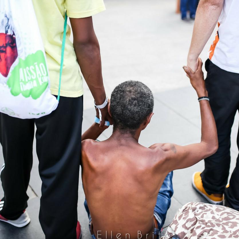 Pobre de rua amparado por dois missionários