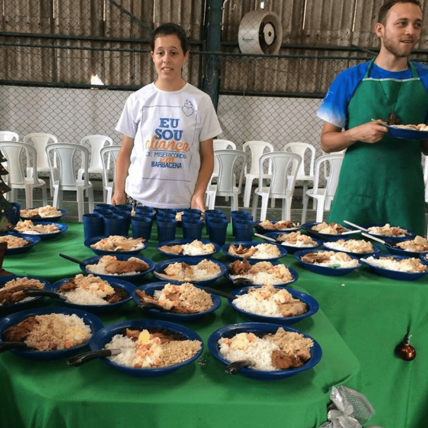 Voluntária ajuda a servir refeições ao povo de rua