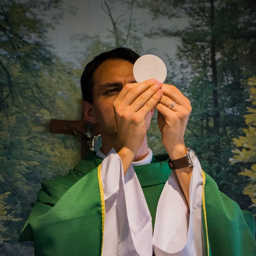 Padre ergue a eucaristia na Missa