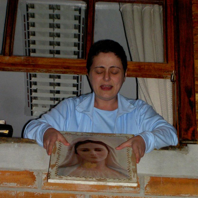 Maria Paola da janela de seu quarto mostra o quadro de Nossa Senhora