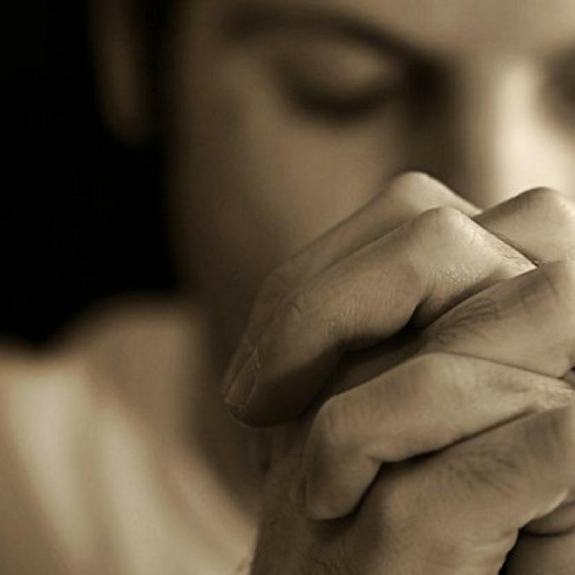 Homem de mãos unidas orando
