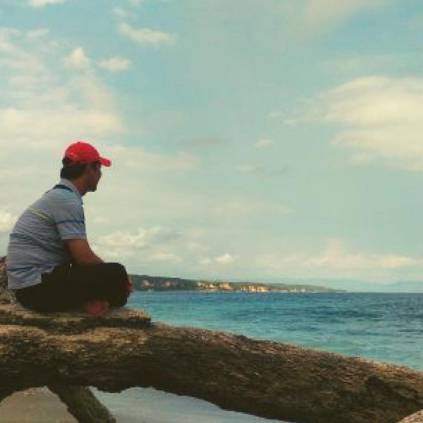 Homem na praia observa o mar