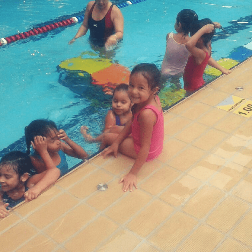 Menina sorri na beira da piscina