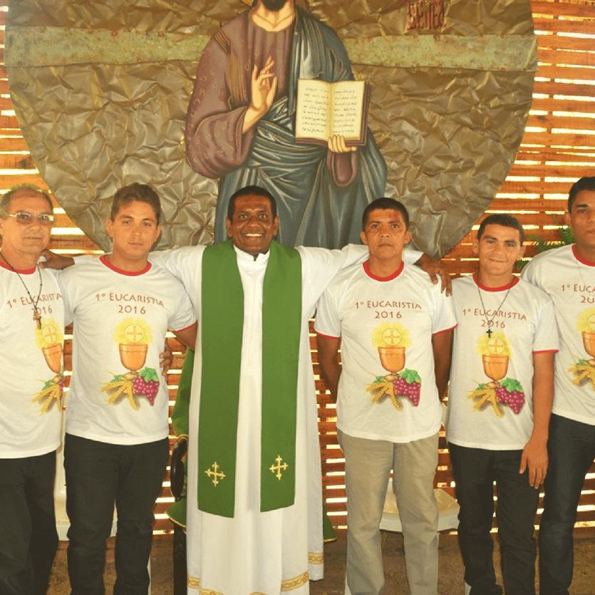 Padre com acolhidos que receberam a primeira eucaristia