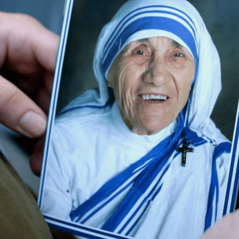 Pessoa segura foto de Madre Teresa