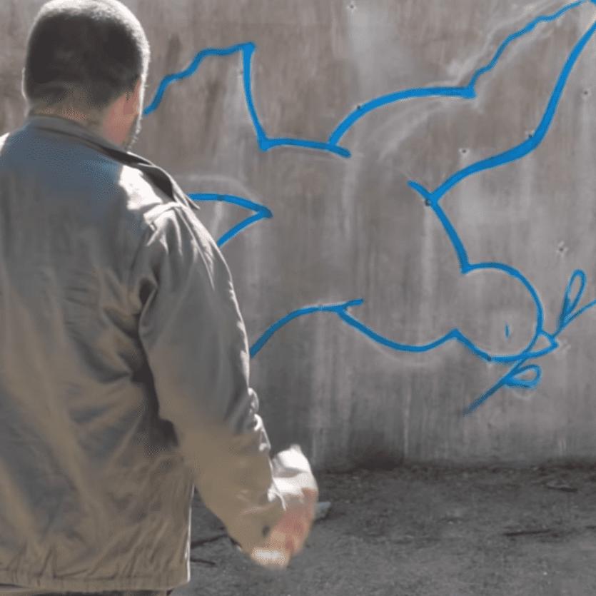 Homem olha para desenho de pomba