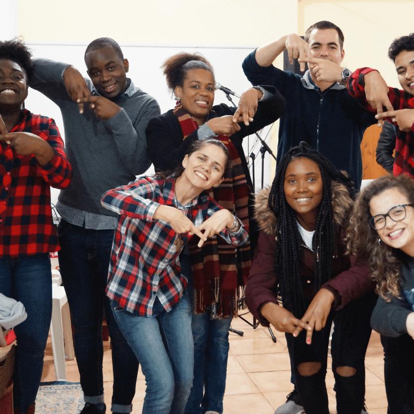 Missionário e jovens fazem o sinal da Geração Acordi
