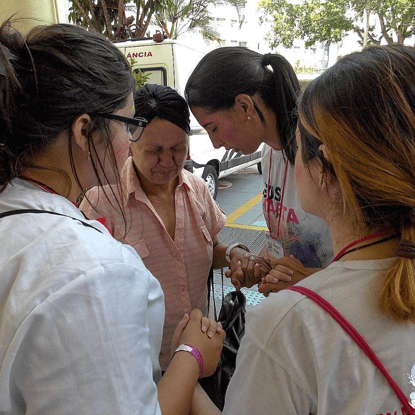 Missionários oram com uma mulher