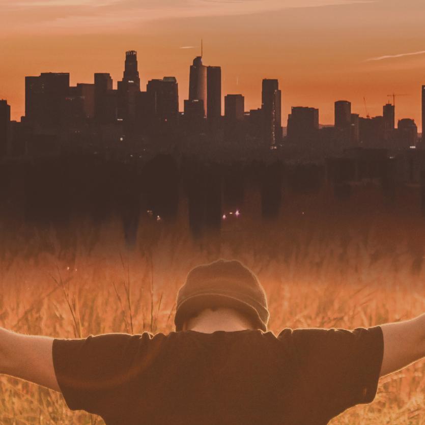 Rapaz de braços aberto sobre a cidade