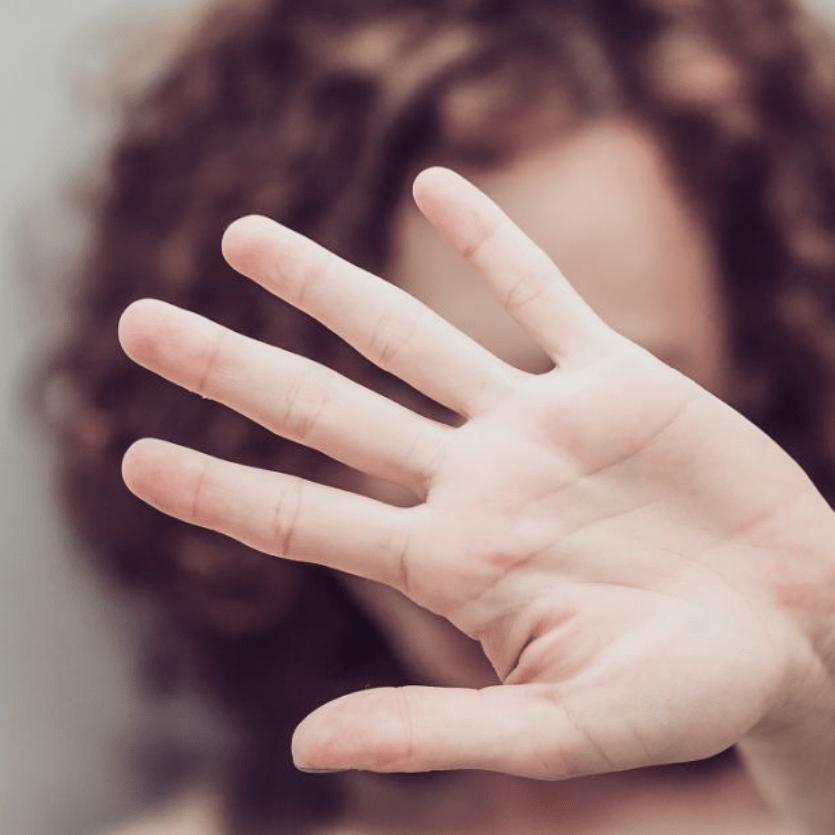 Mulher protege o rosto com as mãos