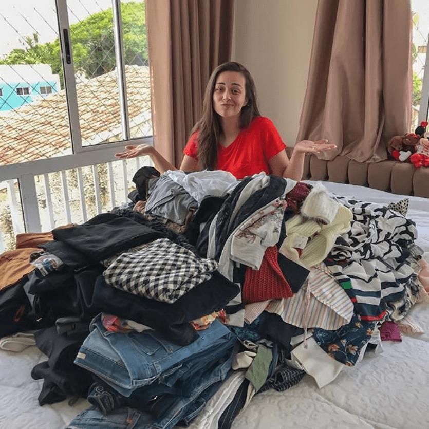 Jovem com muitas roupas em cima da cama