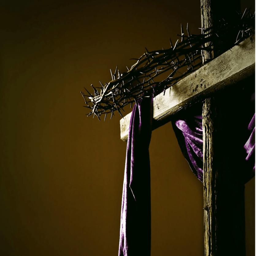 Cruz de Cristo com espinhos e pano roxo.