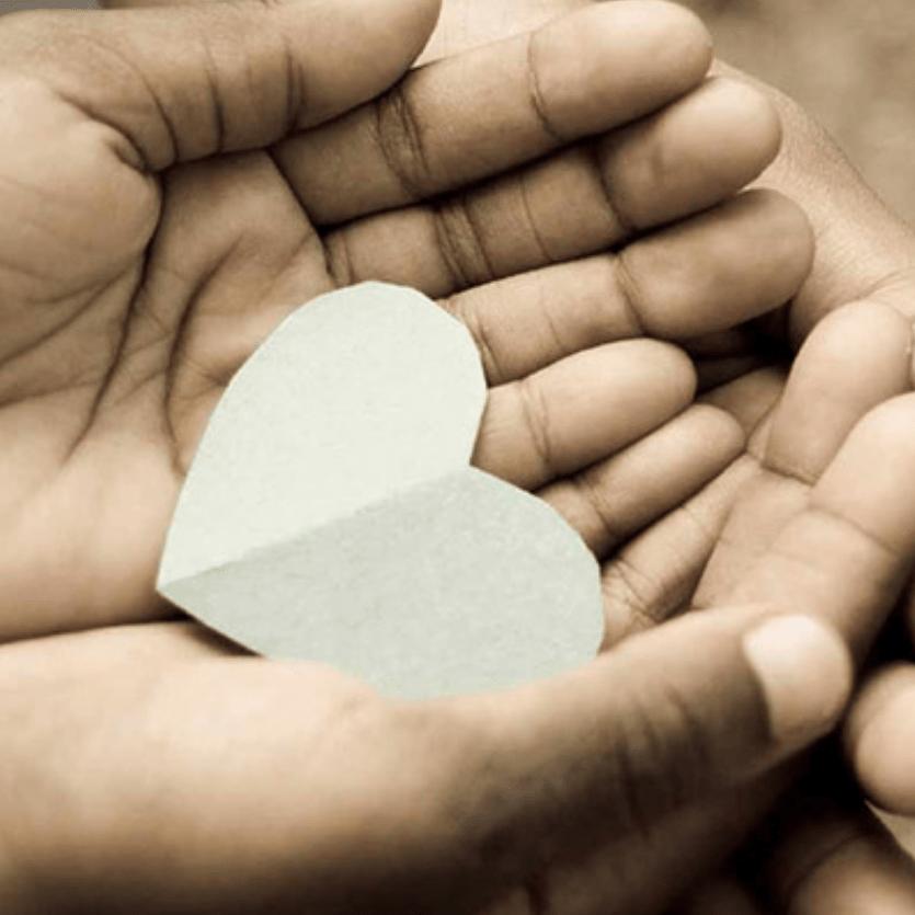 Duas pessoas seguram um coração de papel