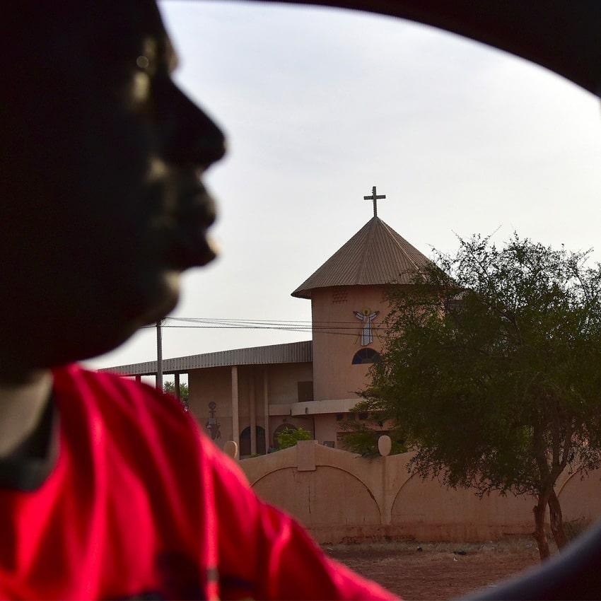 Homem passa de carro em frente a uma igreja
