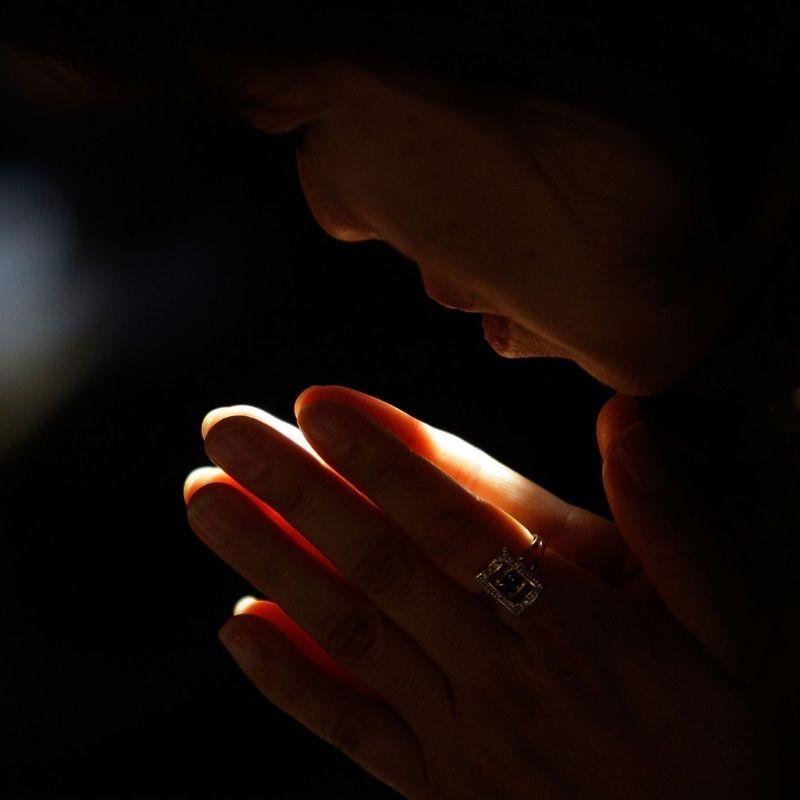 Pessoa ora à luz de velas