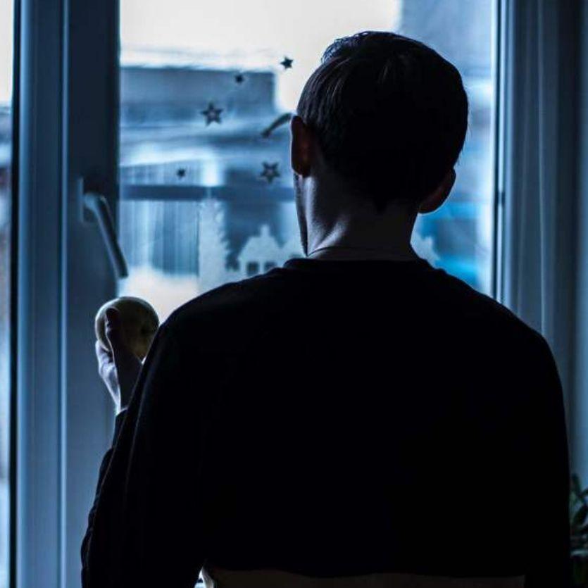 homem olha pela janela de seu apartamento a cidade ao fundo