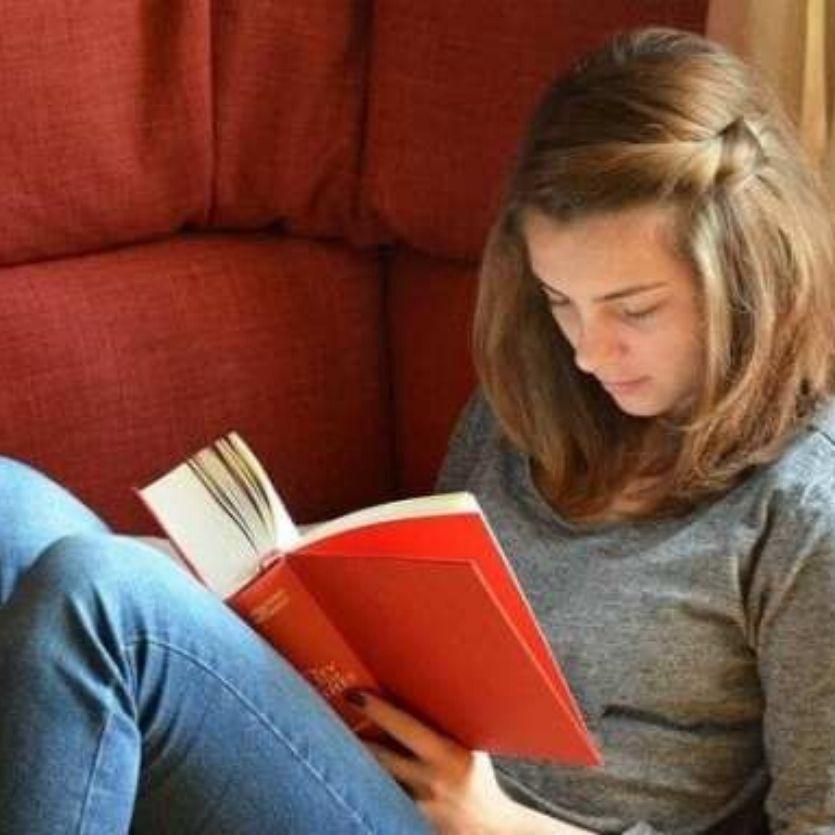 garota-loira-sentada-no-sofá-vermelho-lê-livro