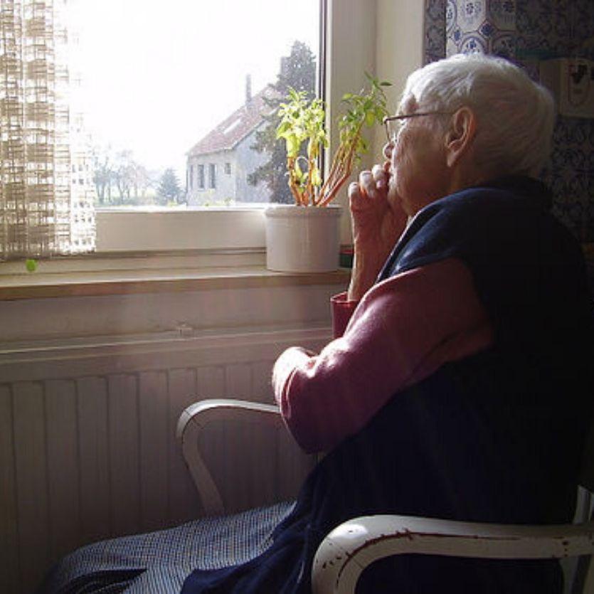 idosa-sentada-na-cadeira-olha-pela-janela