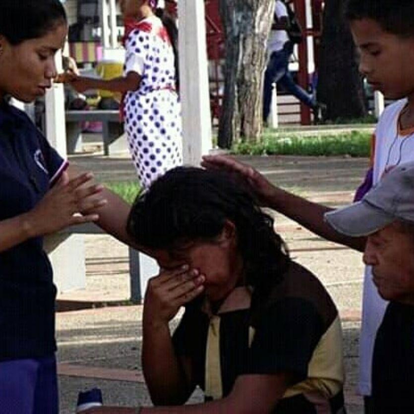 Três missionárias rezam por mulher que chora.