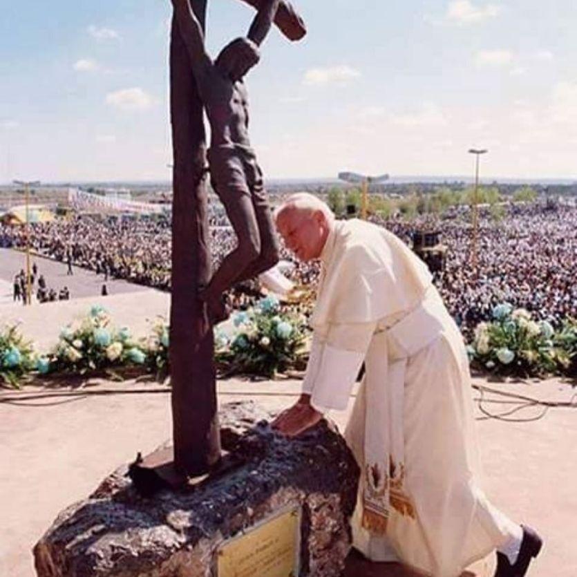São João Paulo II ajoelhado em frente ao crucifixo.