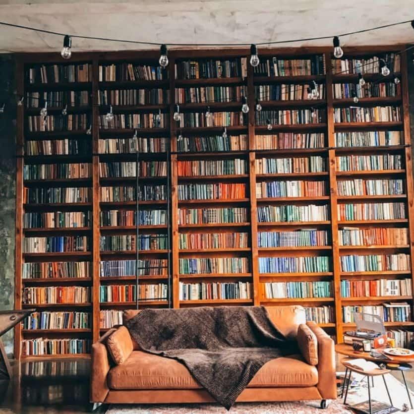 Biblioteca com um sofá marrom