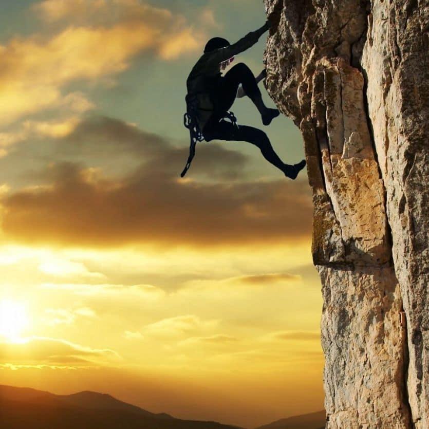 Mulher escala uma montanha ao fundo o pôr do sol