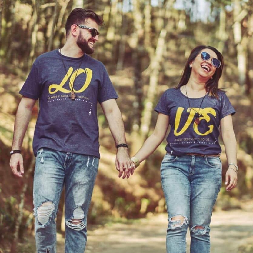 Casal anda de mãos dadas por um caminho de árvores