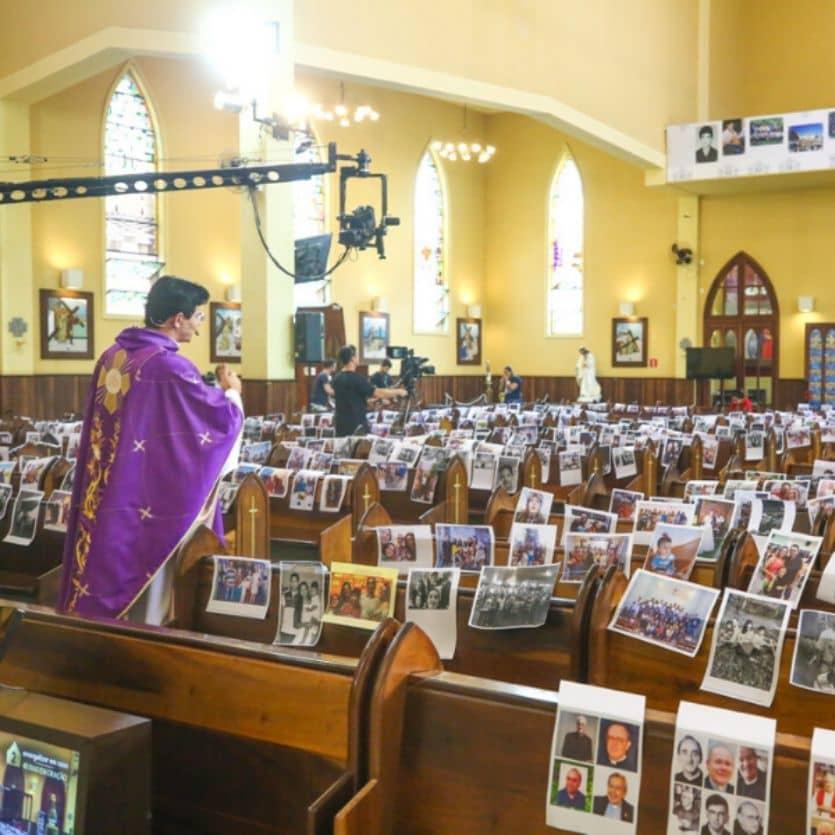 Padre celebra numa igreja cheia de fotos dos fiéis